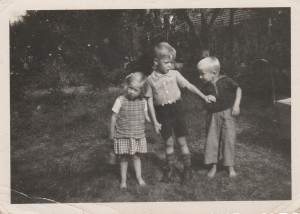 At three years of age with same cousin Eva and her brother Paul. This time bare-footed. Fruit trees in background?
